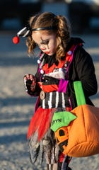 Jaidyn Butler, 8, dressed as a killer clown, looks at some of her trick-or-treating haul.