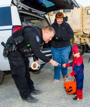 Cruz Perez, 2, dressed as Spiderman, takes a sticker from Yerington police officer Brandon Coombs.