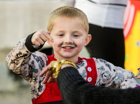 Maurice Galvin, 4, dressed as a strongman, has his fortune told at a trunk-or-treat stop.