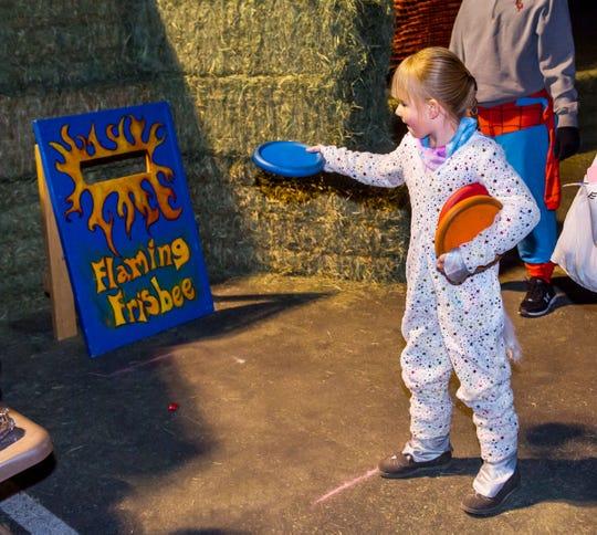 "Hannah Stockton, 6, plays the ""Flaming Frisbee"" toss at Yerington Vineyard Fellowship's Night of Light event."