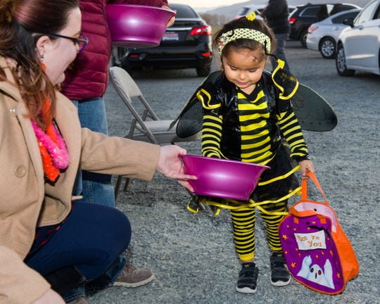 Allison Bobb, 4, dressed as a bumble bee, gets some candy from Sarah Weishaar.