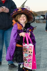 Makenna Brinkley, 7, dressed as a witch, prepares to look for goodies at the trunk-or-treat event.