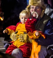 John Montero, warms up with his grandson Steel Montero, 1, by sitting at a fire pit at the Yerington Vineyard Fellowship's Night of Light event.