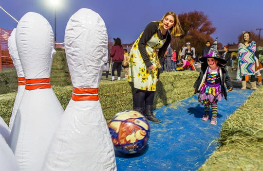 Avery Morris, 4, tries knocking down some giant bowling pins at Yerington Vineyard Fellowship's Night of Light event.