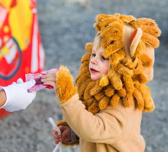 Levi Grissom, 2, dressed as a Wizard of Oz lion, takes a bag of candy while trunk-or-treating at Wild West Chevrolet.