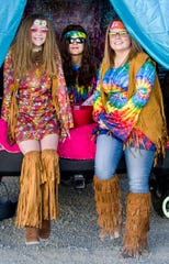 """A trunk-or-treat """"Hippy Halloween"""" group waits for their next visitor."""