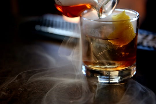 Bartender Mikey Gallardo makes a smoked house Old Fashioned at Masonry Grill in downtown Salem on Oct. 30, 2019. The restaurant in the former Spaghetti Warehouse building opens Friday.