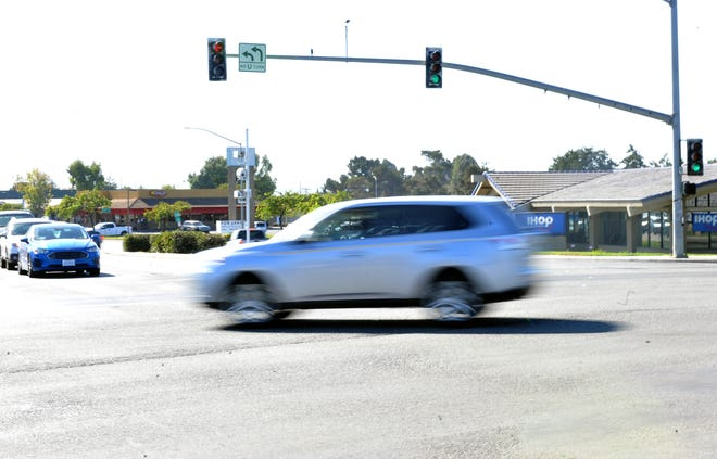 A driver runs a red light at the corner of N. Davis Road and W. Laurel Drive Nov. 1, 2019, the same day that the red-light cameras, on the white tower, were activated at that intersection.