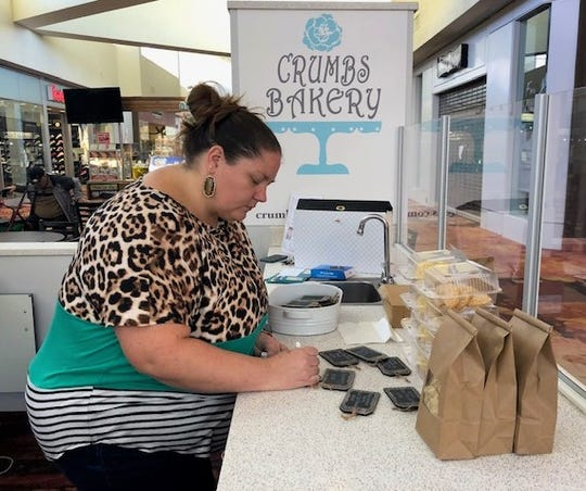 Emily Lloyd, owner, writes out signs for her sweet treats at Crumbs Bakery.