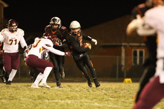 Josh Arlt of Lennox runs the ball as Mitch Williams of Madison defends during Thursday night's playoff game in Lennox.