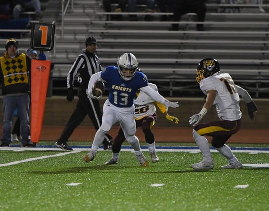 Sioux Falls O'Gorman receiver Zach Norton (13) runs around Harrisburg's Cade Boyer in the Class 11AAA playoff game on Thursday night in Sioux Falls. (Photo by Jon Klemme)