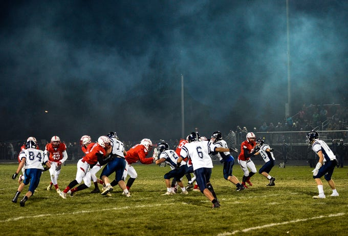 The Burke Cougars play the Britton-Hecla Braves in the class 9A quarterfinals on Thursday, October 31, in Britton as smoke from a nearby grill wafts above the field.