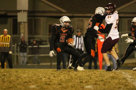 Jackson Arlt (9) looks for running room behind blocking by Caleb Metcalf against Daniel Swenson of Madison during Thursday night's playoff game in Lennox.