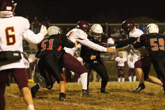 Josh Arlt of Lennox is wrapped up by Cody Brown (71) and Daniel Swenson of Madison during Thursday's playoff game in Lennox.