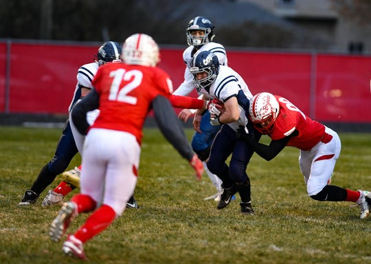 Finn Hanson from Burke is tackled during the class 9A quarterfinals on Thursday, October 31, in Britton.
