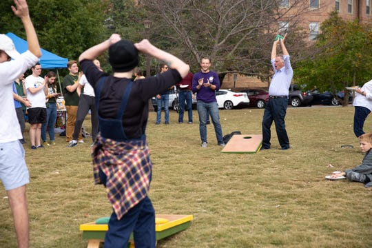 Terry McAuliffe and Josh Roesch celebrate a good shot during a game of cornhole at a tailgate event to promote Del. Michael Mullin , D-Newport New, at the College of William & Mary in Williamsburg, Va.