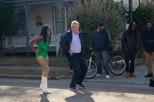 Former Virginia Gov. Terry McAuliffe attempts to join a dance performance during the homecoming parade in Petersburg, Va.