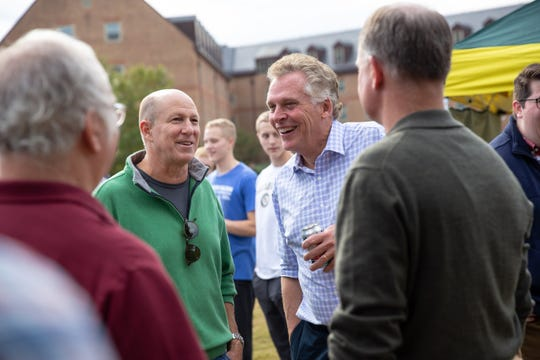 Terry McAuliffe talks with David Lennarz, center left, and others at the tailgate party.