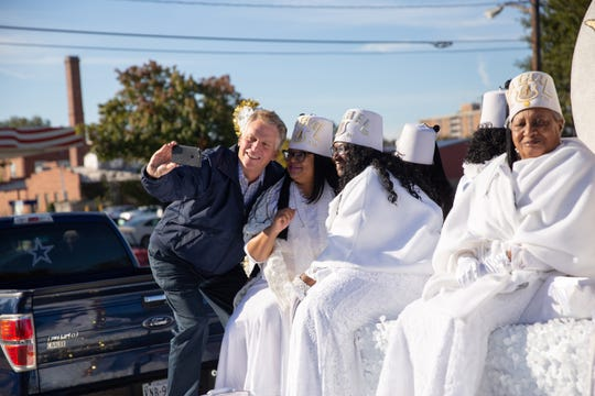 Former Virginia Gov. Terry McAuliffe takes a selfie with members of the Order of the Eastern Star at the homecoming parade in Petersburg, Va.