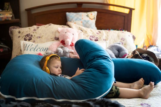 Courtney Zakauska's son Jayden plays on a tablet on her bed in the living room of their home in Marshall, Minn., on Tuesday, Sept. 17, 2019. (Evan Frost/Minnesota Public Radio via AP)