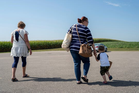 """Jeannie Antony walks to her car with Courtney Zakauska and her son, Jayden, outside of the United Community Action Partnership in Marshall, Minn., on Tuesday, Sept. 17, 2019. Before retiring, Antony worked with Zakauska as a case worker, earning her the title """"Grandma Jeannie."""" (Evan Frost/Minnesota Public Radio via AP)"""