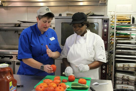 ReFire founder Rebecca Kelly-Manders instructs a student. The eighth cohort of ReFire Culinary began in June 2019.