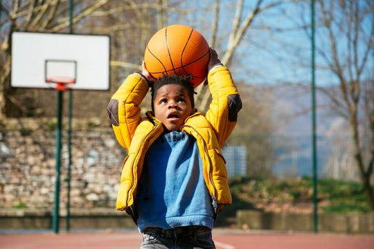 A boy holding a basket ball trying make a basket
