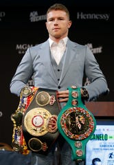 Canelo Alvarez holds up his belts during a news conference Wednesday in Las Vegas. Alvarez is scheduled to fight Sergey Kovalev on Saturday night.