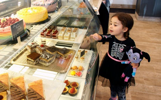 Elena Haven, 3, points to a pastry she'd like to eat at Historia Bakery in Thousand Oaks. Elena visited the new bakery on Halloween.