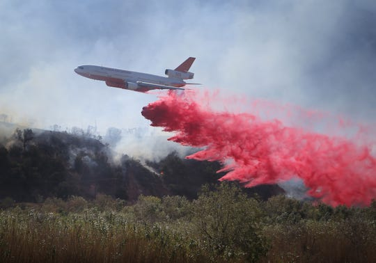 An air tanker drops its load of flame retardant near the Santa Clara River in Santa Paula during the Maria Fire on Nov. 1, 2019.