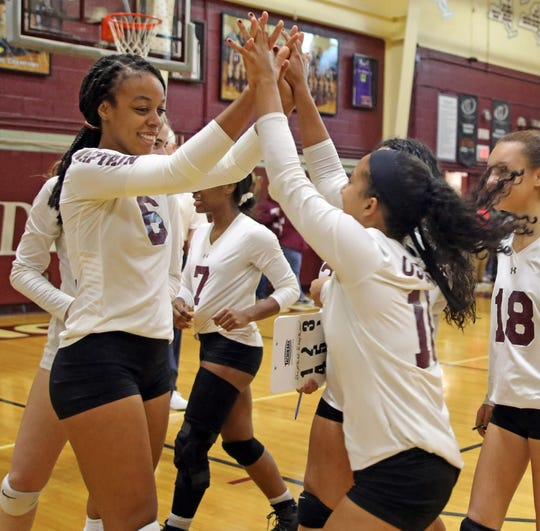 Ossining's Mychael Vernon (6) celebrate with Kristen Pavarini (11) after defeating Ursuline during Section 1 Class AA volleyball quarterfinals at Ossining High School on Nov. 1, 2019.