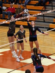 Highland's 	Ashlynn Belcher tips the ball over the net against John Glenn.