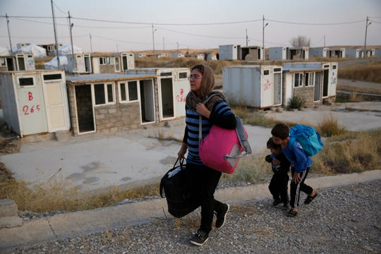 FILE - In this Oct. 17, 2019 file photo, Salwa Hanna with her children, who are newly displaced by the Turkish military operation in northeastern Syria, carry their belongings after they arrive at the Bardarash refugee camp, north of Mosul, Iraq,   For months, every time Turkey threatened to invade northern Syria, Salwa Hanna told her husband they should take their children and flee from the border town of Kobani. And every time, he told her not to worry, because the Americans were there. Now the Christian family is among an estimated 160,000 Syrians who have fled Turkey's offensive, which began last week after President Donald Trump announced he would move U.S. forces out of the way, abandoning their Kurdish allies.  (AP Photo/Hussein Malla) ORG XMIT: CAIDK601