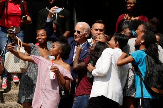 Former Vice President Joe Biden, center, takes selfies and poses for photos with students on the campus of Texas Southern University Friday, Sept. 13, 2019, in Houston.