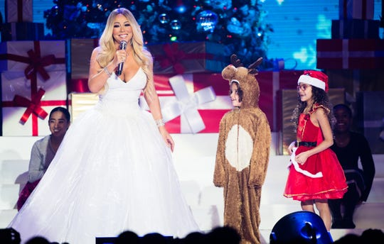 """Mariah Carey, left, with children Moroccan Cannon and Monroe Cannon during last year's """"All I Want For Christmas is You"""" tour in Nottingham, England."""