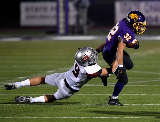 Wylie High running back Noah Beach drags Lubbock Cooper defensive back Carter Bradley before shaking him off during Friday's game at Bulldog Stadium.