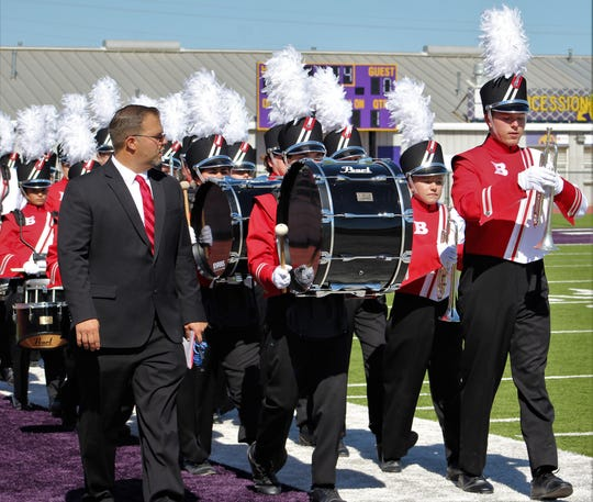 "Baird High School band director Gary Sherman leads his musicians onto the field for their UIL regional contest performance Oct. 21 at Wylie ISD's Bulldog Stadium. Baird earned a ""1"" rating and will compete this week in San Antonio for state honors."