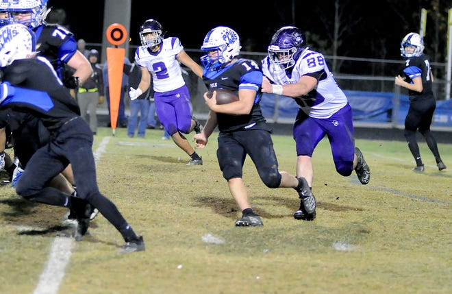 Mitchell's Cole Sparks tracks down Polk County's Angus Weaver during the second half of Friday's game.