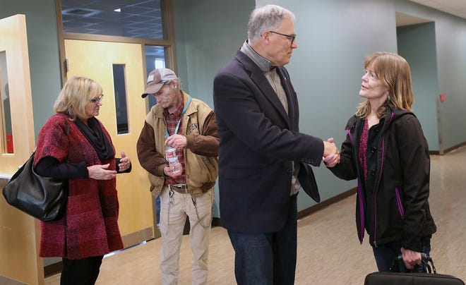 Julie Birkett shakes hands with Gov. Jay Inslee at the Salvation Army in Bremerton on Friday after meeting with city and county leaders to discuss homelessness.