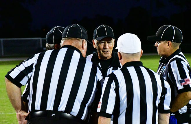 The referees consult each other after a play.