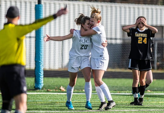 Rice #20 Maris Lynn is embraced by teammate Alex Dostie after scoring to tie the game 1-1 during their girls soccer championship against Harwood on Saturday, Nov. 2, 2019, at South Burlington High School. Rice won, 2-1.