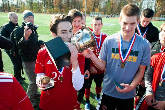 CVU's Asa Lawson (24) kisses the championship trophy during the DI boys soccer championship game between the Mount Mansfield Cougars and the Champlain Valley Union Redhawks at Buck Hard Field on Saturday morning November 2, 2019 in Burlington, Vermont.