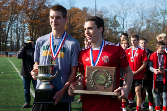 CVU captains poses for a photo with the championship trophy during the DI boys soccer championship game between the Mount Mansfield Cougars and the Champlain Valley Union Redhawks at Buck Hard Field on Saturday morning November 2, 2019 in Burlington, Vermont.