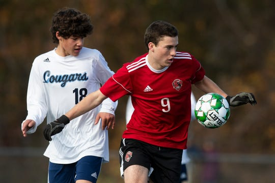 CVU's Jonah Roberts (9) plays the ball in front of MMU;s Easton Fitzhugh (18) during the DI boys soccer championship game between the Mount Mansfield Cougars and the Champlain Valley Union Redhawks at Buck Hard Field on Saturday morning November 2, 2019 in Burlington, Vermont.