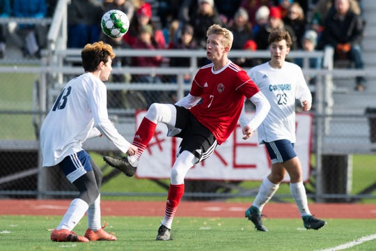 CVU's James Schmidt (7) battles for the ball Jacobs Surks (13) during the DI boys soccer championship game between the Mount Mansfield Cougars and the Champlain Valley Union Redhawks at Buck Hard Field on Saturday morning November 2, 2019 in Burlington, Vermont.
