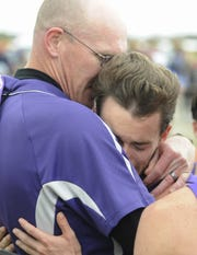 Unioto head coach Matt Paxton hugs senior Eric Hacker after Unioto finished second overall at the Division II OHSAA State Cross Country Championships on Nov. 2, 2019 at National Trail Raceway in Hebron, Ohio.