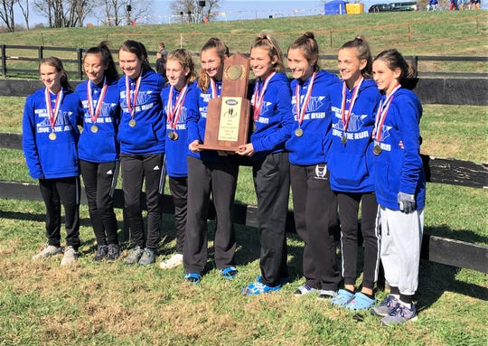 The Scott Eagles cross country team celebrates with their team championship trophy.