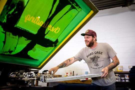Brandon Swinehart of Wyoming, screen-presses T-shirts the shop he co-founded with his wife, SRO Prints, in Evendale. Swinehart has been in recovery for about 14 years and hires people with addiction to give 'second chances.'
