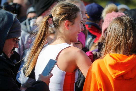 Ames senior Camille Jackson is hugged by friends and family after winning a title in Class 4A during the 2019 Iowa high school boys and girls state cross country meet on Saturday, Nov. 2, 2019, in Fort Dodge.
