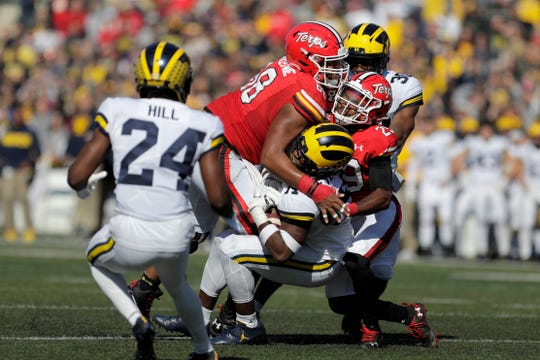Michigan defensive back Josh Metellus, center bottom, is brought down by Maryland offensive lineman Ellis McKennie (68) and wide receiver Sean Savoy (29) after Metellus intercepted a pass from quarterback Josh Jackson during the first half of an NCAA college football game, Saturday, Nov. 2, 2019, in College Park, Md.